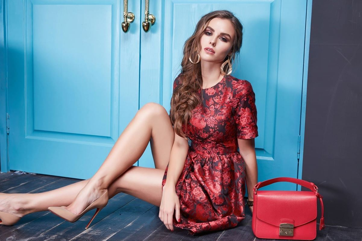 Beautiful young sexy woman lady in elegant evening dress red silk dress new stylish fashion collection long brown hair, shoes, interior blue door in bedroom room meeting, party style brand lather bag