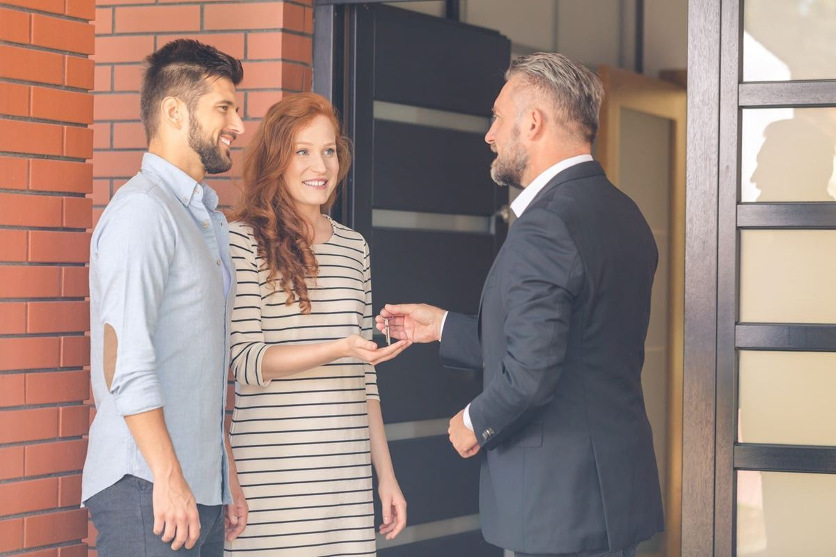 Man in black suit giving keys to a flat for rent to smiling young students